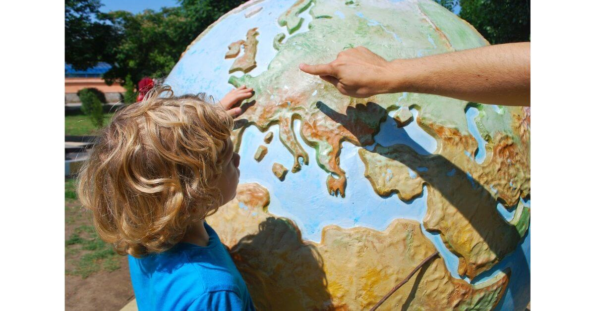 a good teacher trying to teach world map creatively in a big globe